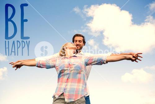 Composite image of happy couple standing outside with arms stretched kissing