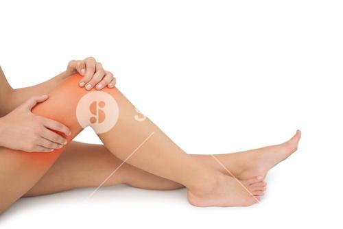 Mid section of young woman sitting on floor touching her injured knee