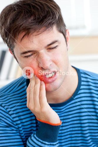 Portrait of a man having a raging toothache sitting in the livingroom