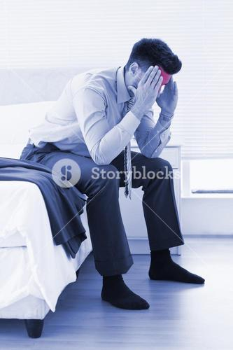 Hungover businessman sitting at edge of bed