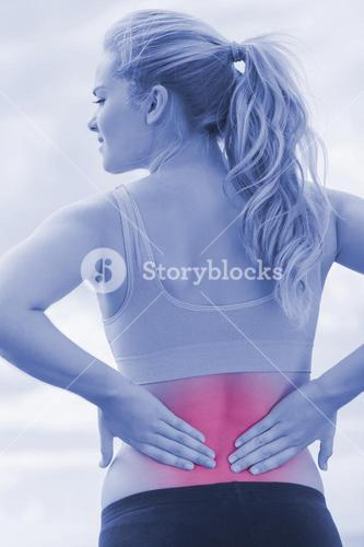 Rear view of healthy woman suffering from back pain on beach