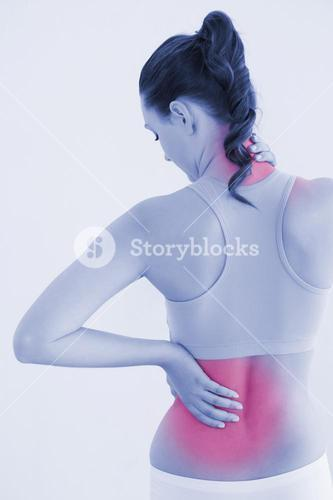 Rear view of a toned woman with back pain against wall