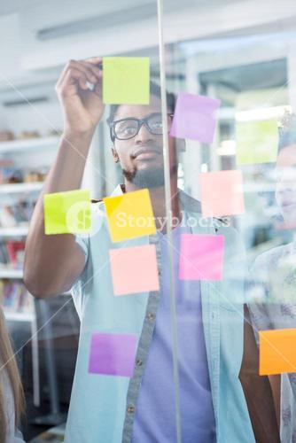 Creative businessman writing on adhesive note