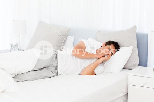 Sick man blowing his nose lying on his bed
