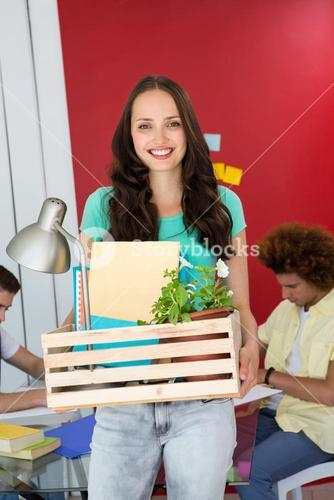 Casual businesswoman carrying her belongings in box