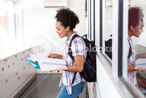Casual young woman reading folder in office