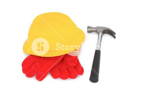 Yellow hardhat with protective gloves and hammer