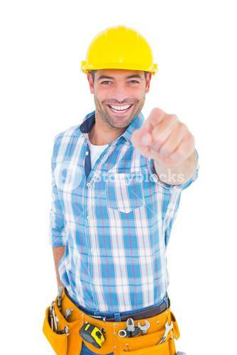 Portrait of smiling handyman pointing at you