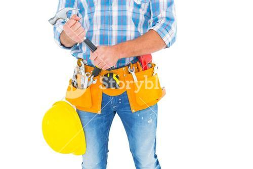 Midsection of manual worker holding hammer