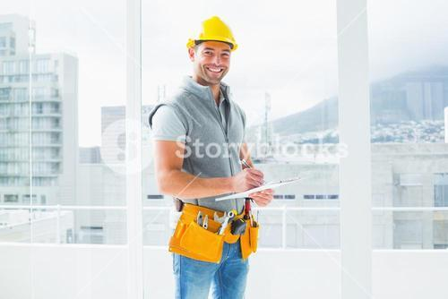 Manual worker writing on clipboard in building