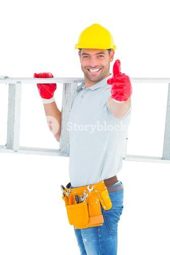 Smiling handyman carrying ladder while gesturing thumbs up