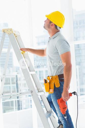 Handyman with drill machine climbing ladder in building
