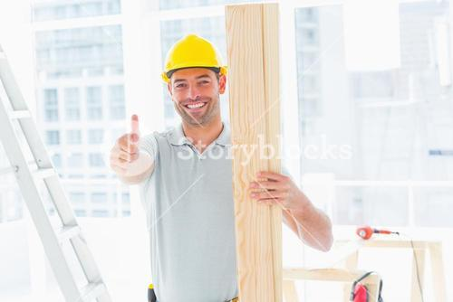 Carpenter holding plank while gesturing thumbs up in building