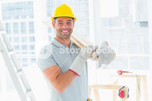 Manual worker carrying planks in building
