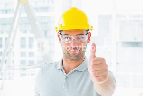 Manual worker gesturing thumbs up at site