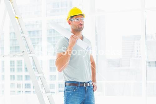 Handyman holding rolled up blueprint in bright office