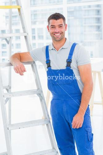 Happy handyman in overalls leaning on ladder at office