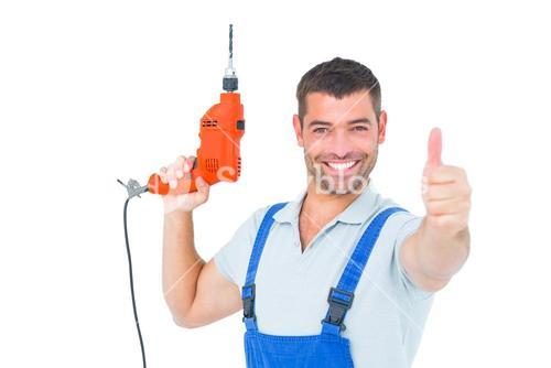 Smiling repairman with drill machine gesturing thumbs up