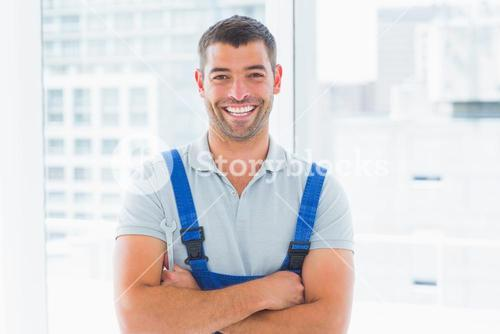 Portrait of smiling handyman standing arms crossed in office