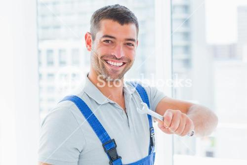 Smiling manual worker holding spanner in office