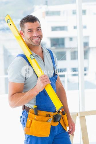 Happy repairman in overalls holding spirit level in office