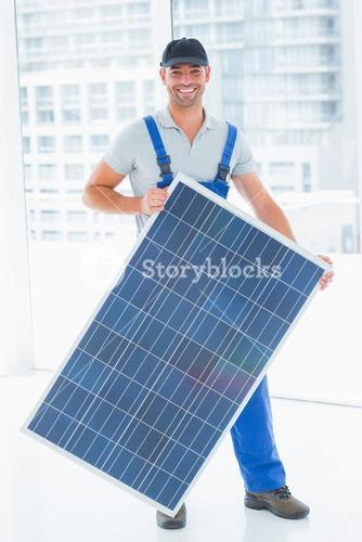 Manual worker holding solar panel in bright office