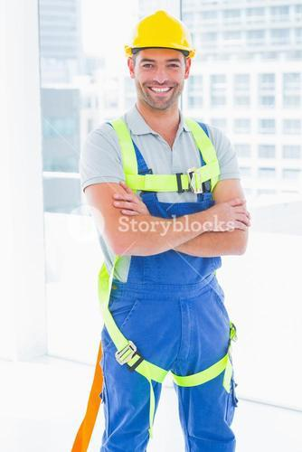 Manual worker wearing safety harness in bright office