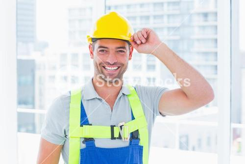 Happy manual worker wearing yellow hard hat