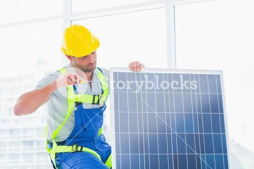 Worker tightening solar panel in office