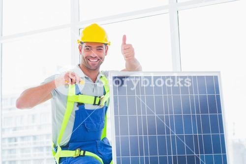 Male worker tightening solar panel while gesturing thumbs up