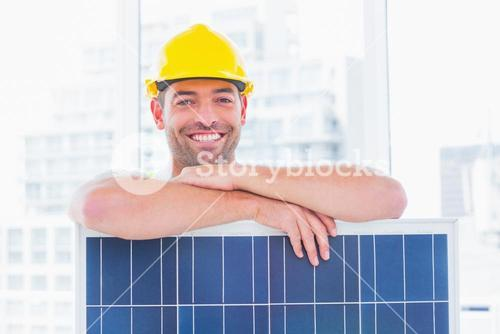Smiling manual worker with solar panel in office