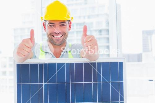 Smiling manual worker with solar panel gesturing thumbs up