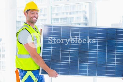 Manual worker carrying solar panel at office