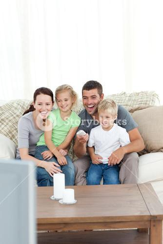 Happy family laughing while watching television sitting on the sofa