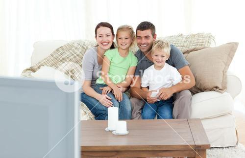 Adorable family watching television together sitting on the sofa