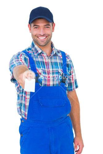Portrait of happy handyman giving visiting card