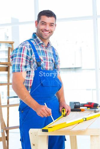 Smiling handyman using tape measure at workbench in office
