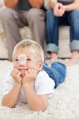 Cute little boy lying on the floor and watching television with his parents
