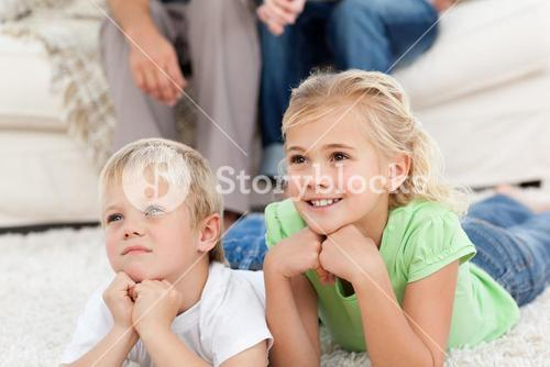 Brother and sister watching television on the floor with their parents