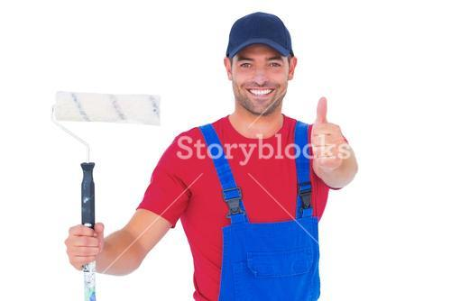Smiling handyman with paint roller gesturing thumbs up