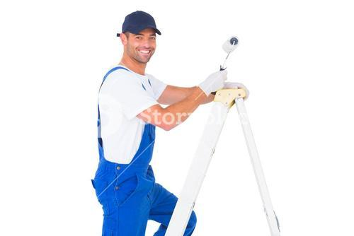 Happy handyman with paint roller climbing ladder