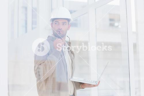 Architect holding laptop while looking away in office