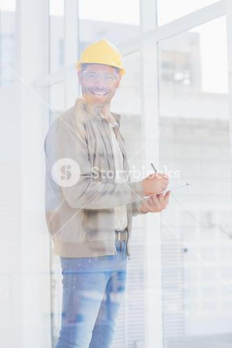 Architect writing on clipboard in office