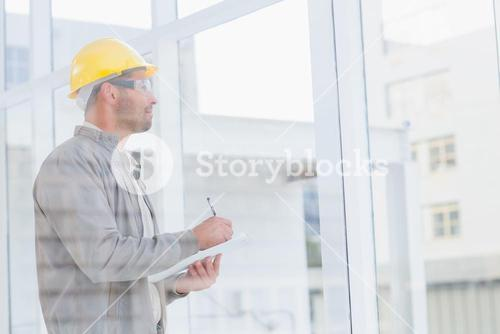 Architect writing on clipboard while looking through office window