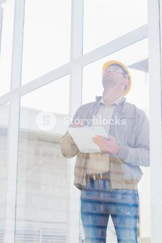 Supervisor looking up while writing on clipboard
