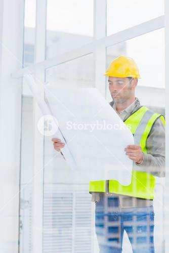Architect reading blueprint in office