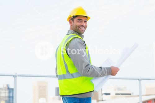 Architect in protective clothing holding blueprint outdoors