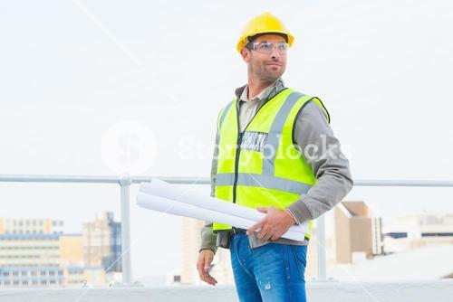 Architect holding rolled up blueprints outdoors