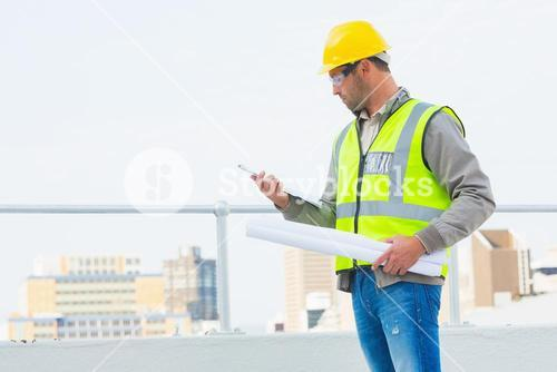 Architect with blueprints reading clipboard outdoors