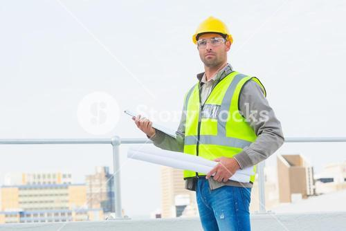 Architect holding blueprints and clipboard outdoors